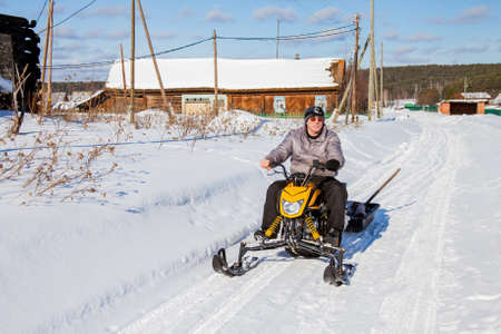 Man on a snowmobile is riding around the village, Sverdlovsk Region, Russia Stock Photo