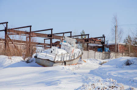 old items: Perm, Russia - March 11.2017: An old boat on the snow in the backwaters of the Kama river