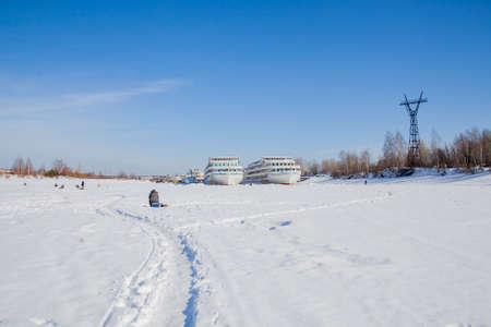 Perm, Russia - March 11.2017: Fishermen catch fish on a frozen river in winter