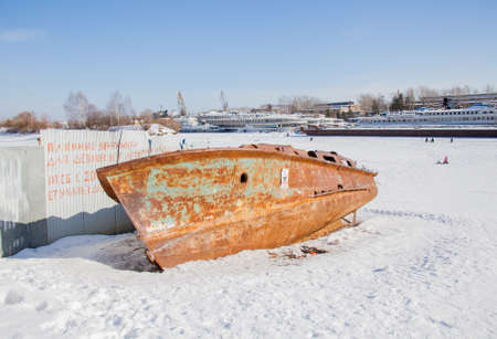 Perm, Russia - March 11.2017: The rusty boat hull on a winter day lies on the snow in the backwaters of the Kama River