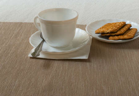 white tea Cup and saucer with biscuits on the table