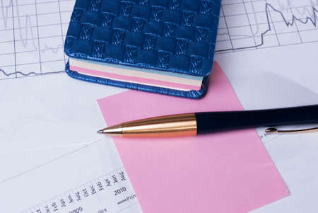 calibrated: Pen lying on financial statements. Business Background Stock Photo