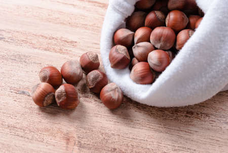 untreated: The untreated nuts in shell in bag on wooden Board