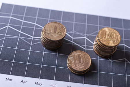 dept: Coins on financial charts. Business and financial concept Stock Photo