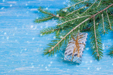 Gift box on a spruce branch on a wooden background Stock Photo