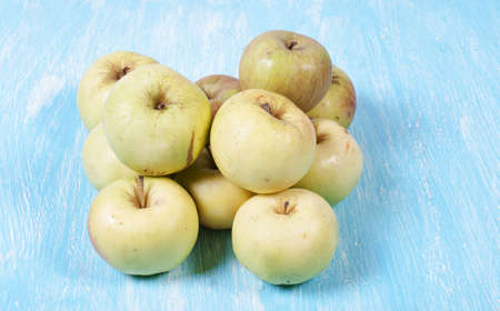 Whole green apples lie on a wooden background