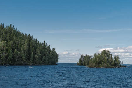 The island in the lake covered with trees. Stock Photo