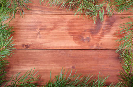 Spruce branches in the form of a frame on a wooden background