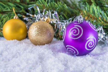 Christmas balls on snow. Background of Christmas tree branches and tinsel. With congratulatory text Stock Photo