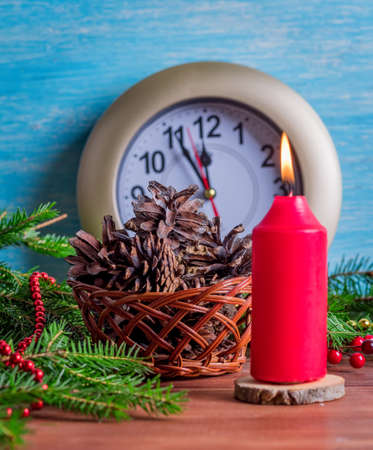 Watch with the last minutes of the outgoing year, a large red candle and a basket of cones. Stock Photo
