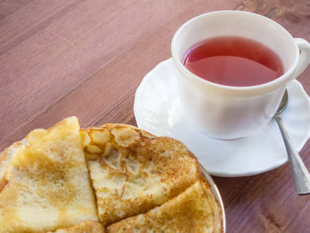 Cup with tea and a plate with pancakes on a wooden table Stock Photo