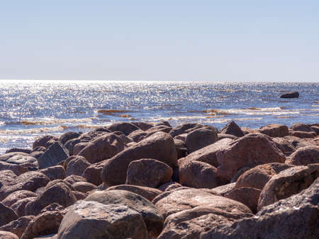 Boulders on a sandy beach. A shore of a lake. Stock Photo