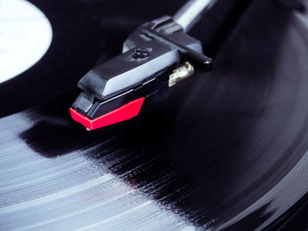 Vinyl record player needle above a rotating disc. Audio equipment for nightclubs