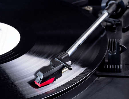 Vinyl record player needle above a rotating disc.