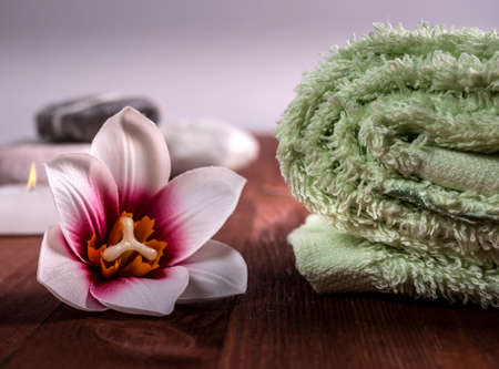 Rolled up green towel, orchid flower on the tree and stones in the background