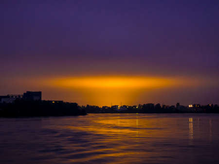 Dark blue sky with yellow city lights. View from the river Stok Fotoğraf
