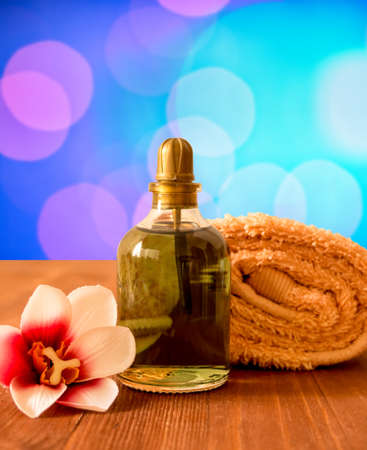 Set on for spa and wellness. Rolled towel, bottle of oil and orchid flower on a wooden background.