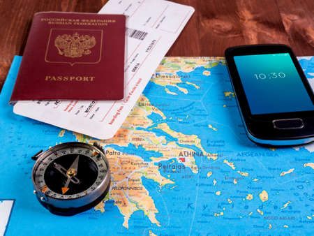 Passport with boarding passes, a compass and a smartphone with a white screen on the map
