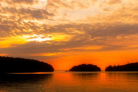 Sunset on the water. Beautiful sky and silhouettes of islands on the horizon Stockfoto