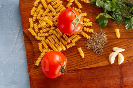 Set for cooking pasta. Tomatoes, pasta, garlic, basil and spices on the kitchen board Stockfoto