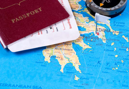 Passport with tickets, compass on a tourist map with pushpins. Close-up