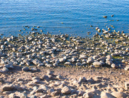 the river bank, the sea covered with pebbles. stone shore and water