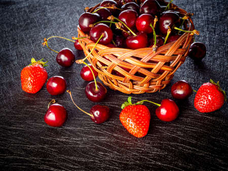 Harvested fresh cherry and strawberries in a basket on a black backgroundsh cherries and strawberries Stockfoto