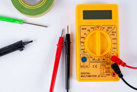 Multimeter, soldering iron and screwdriver on a white background