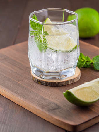 Cocktail with lime and mint leafs on wooden background