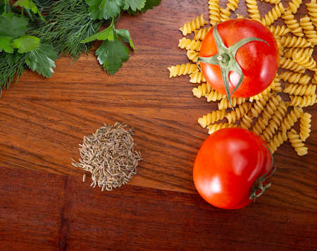 Ingredients for cooking food on the kitchen board. Tomatoes, Basil, Pasta and Spices Stockfoto