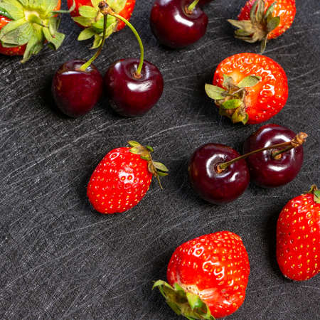 Fresh cherries and strawberries on a black background
