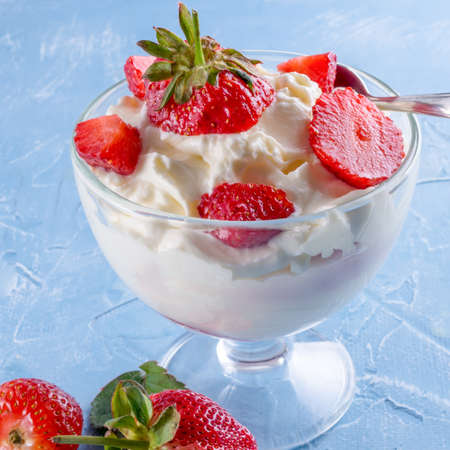 Ice cream in bowl with strawberries on blue background