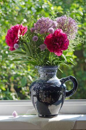 windowsill: A bouquet of flowers in a blue jug on the windowsill of the open window.