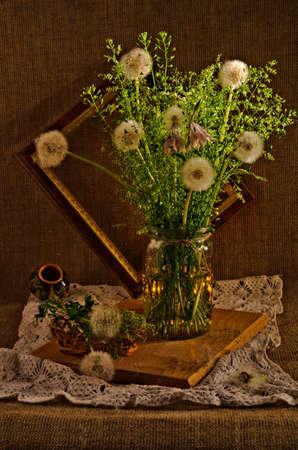glass jar: A bouquet of dandelions in a glass jar.