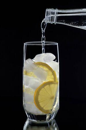 vaso de agua: El agua mineral se vierte de una botella en un vaso con hielo y lim�n.