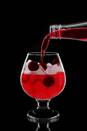 �cherry: The cherry cocktail is poured from a bottle into a glass with ice and a cherry, on a black background. Foto de archivo