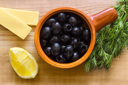 Black olives in a Cup, cheese, a slice of lemon and dill on wooden table