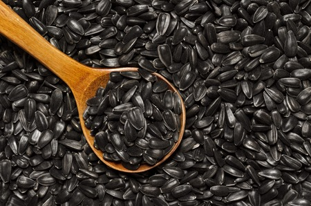gnaw: Selected sunflower seeds in a wooden spoon lying on the layer