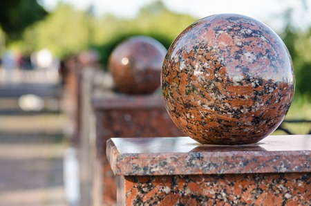granite park: Granite balls on fence in urban Park