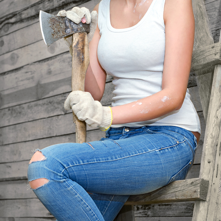axe girl: Girl sitting on an old ladder against the wall from the old boards. In old clothes and work gloves, holding an old axe.