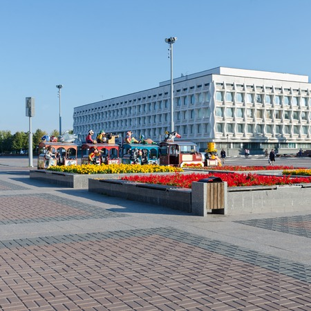 flower beds: State University in Ulyanovsk, Russia. Located on the square with flower beds and childrens rides. People in the distance.