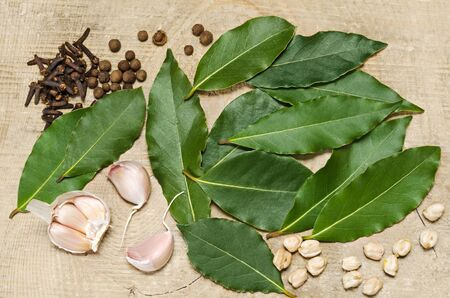 Bay leaf and pepper with cloves, lying on a wooden background . Stock Photo