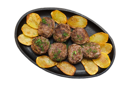 cast iron pan: Fried meatballs with rice and French fries in a cast iron pan isolated on white background.