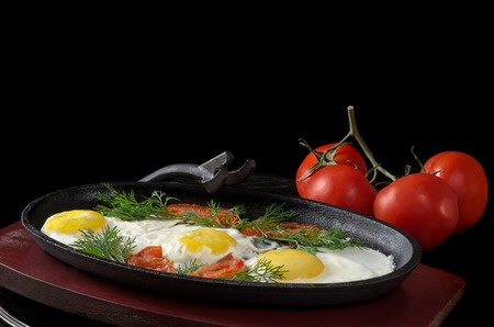 cast in place: Scrambled eggs with tomatoes in a frying pan on the stand,and the whole tomatoes on black background