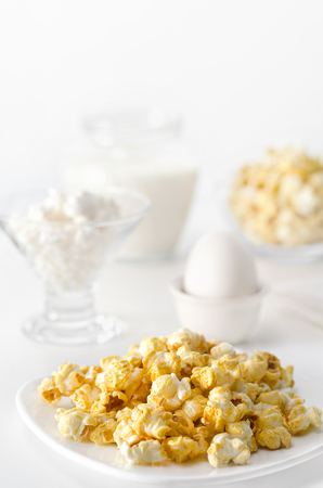 high key: Breakfast white on white, high key and bokeh. A bowl of popcorn, eggs, cheese and milk.