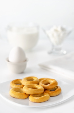 high key: Breakfast white on white, high key and bokeh. A bowl of crackers, eggs, cheese and milk.