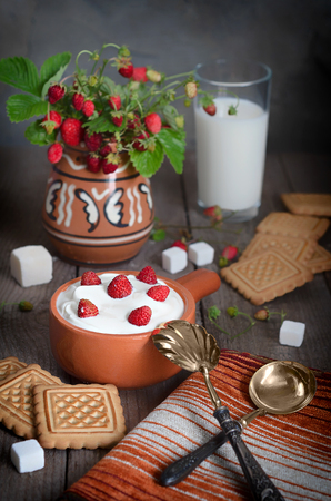 silver plated: Strawberry with cream in a ceramic Cup, cookies and milk in glass on old wooden surface. Bouquet with strawberries in a ceramic vase and antique spoons on a napkin. The rustic style. Stock Photo