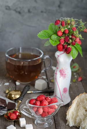silver plated: Strawberries in a glass Cup and a bouquet of wild strawberries in a vase. White bread crumb, antique spoons and tea, rustic Style, background blur.