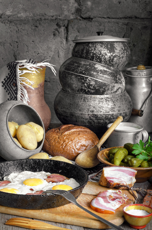 antique dishes: Bacon and eggs, boiled potatoes, pickles. On the background of antique dishes and bread.
