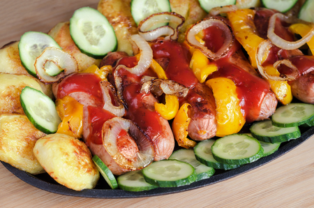 potato tree: Sausage on a platter with ketchup, roasted potatoes,peppers and onions. Slices of fresh cucumber, wooden background. Stock Photo